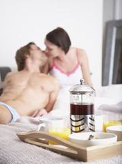 Couple with breakfast in bed kissing