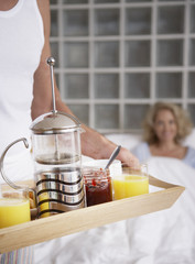 Man bringing woman breakfast in bed