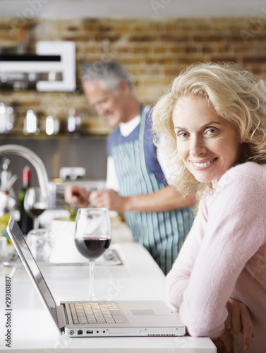 Woman on laptop with wine and man in background preparing salad