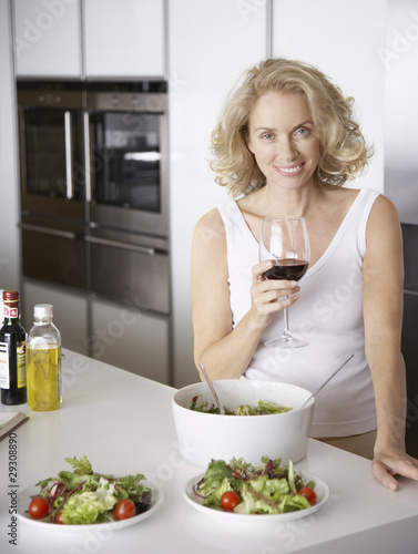 Woman standing with wine by bowls of salad