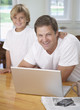 Man and young boy in kitchen with laptop