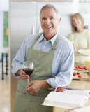 Couple in kitchen preparing meal and drinking wine
