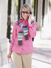 Woman outdoors with shopping bags and her mobile phone
