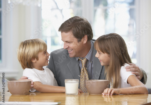 Man and two young kids in kitchen bonding