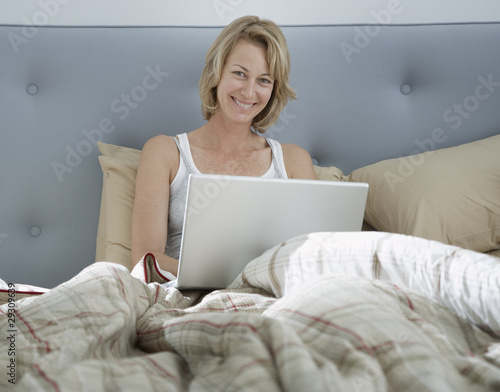 Woman sitting in bed using laptop