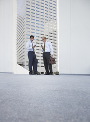 Two businessman standing outdoors looking at their mobile phones