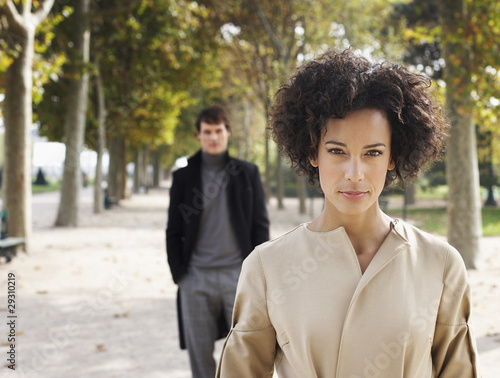 Businesswoman outdoors in park with businessman behind her