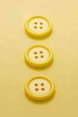 並べた黄色のボタンのアップ
