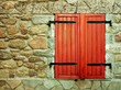 Red shutter window in many textured stone wall