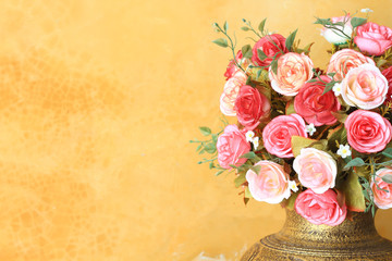 Pot of romantic pink roses on vintage painted background