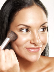 Mujer latina maquillándose,