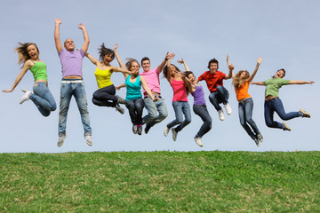 group of happy kids or teens jumping