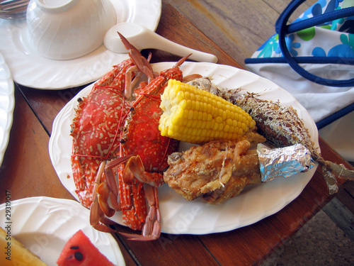 Dish in Thailand - crabs with corn, fish, a hen and greens.