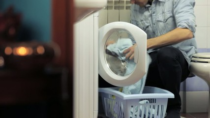 man using washing machine, doing chores