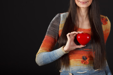 Young female holding heart shape on dark background