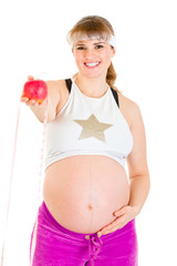 Smiling beautiful pregnant woman holding measure tape and apple