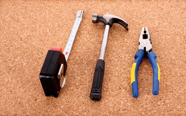 Hammer, pliers and ruller on cork board surface