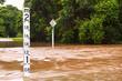 Leinwandbild Motiv Flooded road with depth indicators in Queensland, Australia