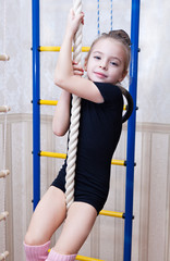 a beautiful girl climbs on a rope