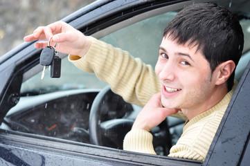 Happy young man showing his car keys