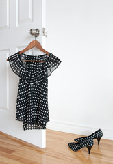 Polka dot blouse on a hanger and shoes on the floor