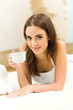 Portrait of young woman drinking coffee, at home