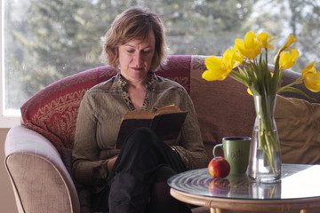 Female reading book by table with daffodils