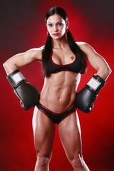 Fit female boxer swings a punch