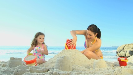 Beautiful mother helping her daughter to build a sand castle