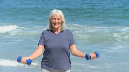 Elderly woman working his muscles with dumbbells