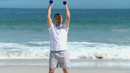 Elderly man working his muscles with dumbbells
