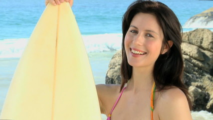 Beautiful woman looking at the camera with a surfboard