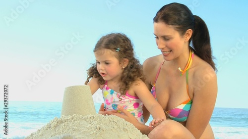 Beautiful mother playing with her daughter on the sand