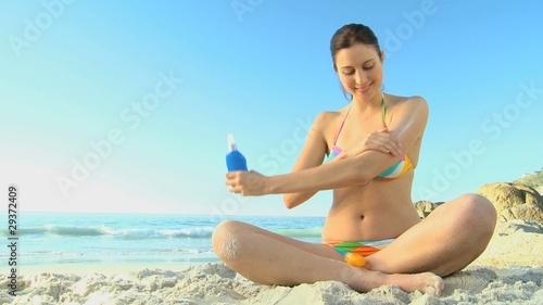 Beautiful woman putting sunscreen on herself