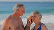 Elderly couple listening to a seashell