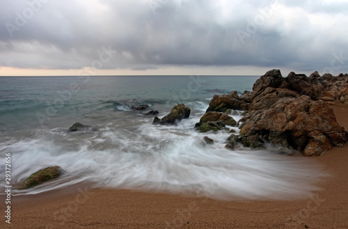 Seascape with motion blurred waves hitting the rocks