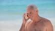 Elderly man listening to a seashell