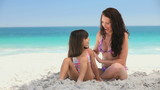 Attractive mother putting sunscreen on her daughter
