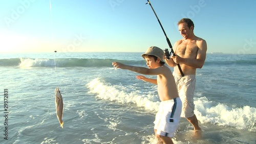 Man fishing with his son on the beach
