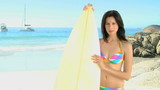 Woman looking at the camera with a surfboard