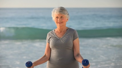 Aged woman working his muscles with dumbbells