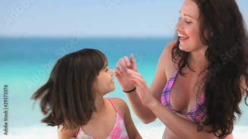 Beautiful mother putting sunscreen on her daughter