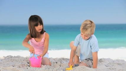 Cute children building a sand castle