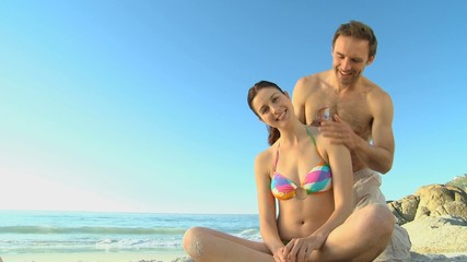 Man putting sunscreen on his girlfriend