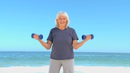 Senior woman working his muscles with dumbbells