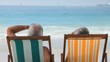 Elderly couple looking at the ocean sitting on beach chairs