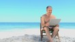 Elderly man using a laptop sitting on beach chairs