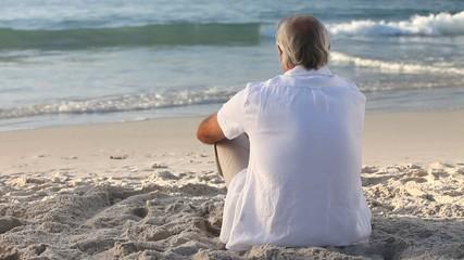 Elderly man looking at the ocean