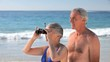Elderly couple looking through binoculars