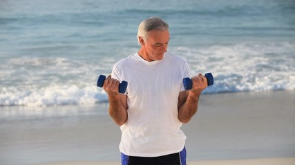 Elderly handsome man working his muscles with dumbbells